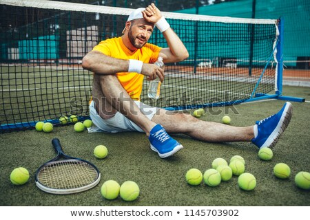 Smiling exhausted sportsman holding water bottle while resting Stock photo © deandrobot