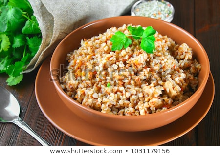Stock photo: Raw buckwheat in wooden bowl and spoon. Groats in wood dish and