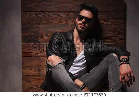 seated fashion man in leather jacket resting elbow on knee Stock photo © feedough