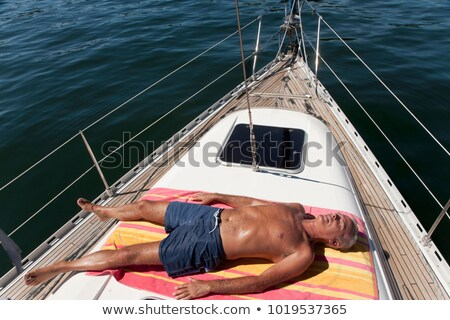Mature man swimming in sea by yacht Stock photo © IS2