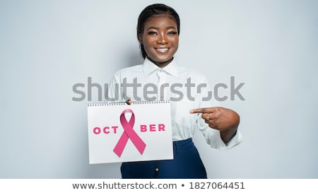Woman pointing at pink ribbon for breast cancer awareness on white background Stock photo © wavebreak_media