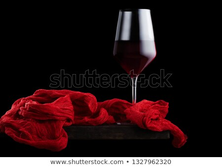 Elegant glass of red wine with red vintage cloth on wooden board on black background. Space for text Stock photo © DenisMArt