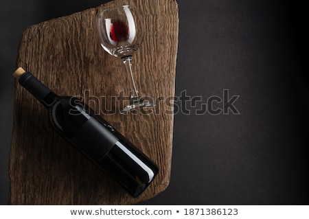 Glass and bottle of red wine with dark grapes on wooden board on black background. Space for text Stock photo © DenisMArt