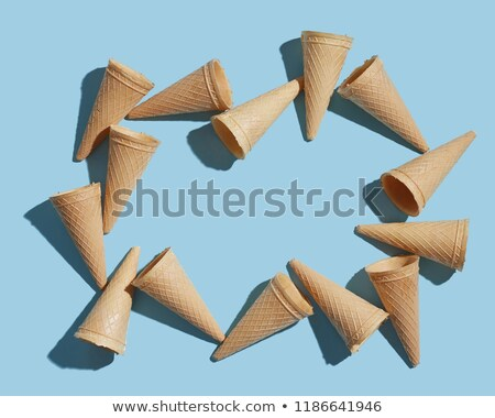 The pattern of wafer ice cream cones empty with shadows on a pastel blue paper. Flat lay. Stock photo © artjazz