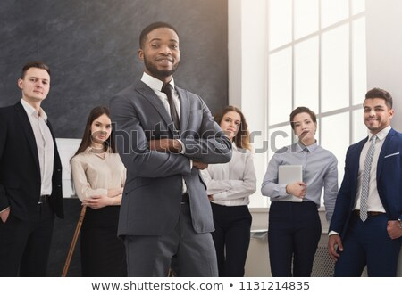 portrait of smiling businessman standing with hands folded stock photo © feedough