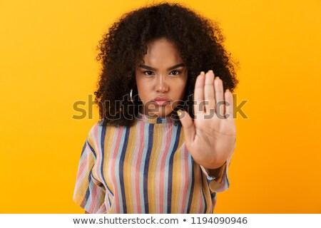 Displeased young african cute girl posing isolated over yellow background make stop gesture. Stock photo © deandrobot