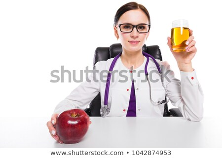 Female nutritionist holding apple and glass of fresh juice in her hands on white background Stock photo © Traimak