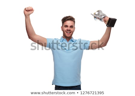 portrait of young man wearing polo shirt celebrating with trophy Stock photo © feedough