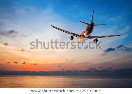 Airplane flying in the sunset sky, travel background Stock photo © lightpoet