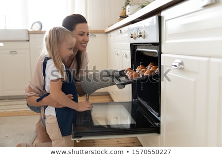 Mother Taking Cupcakes Out From Oven Stock photo © AndreyPopov