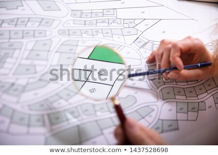 Human Hand Holding Magnifying Glass Over Cadastre Map Stock photo © AndreyPopov