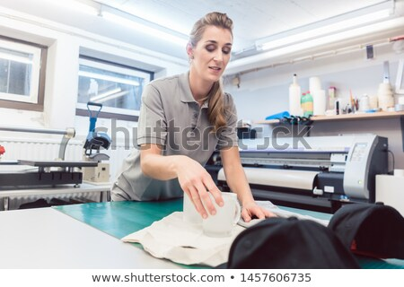 Woman putting promotional items in a set Stock photo © Kzenon