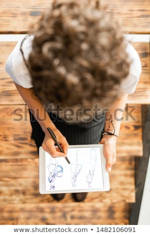Zdjęcia stock: Overview Of Young Female Fashion Designer Pointing At One Of Model Sketches