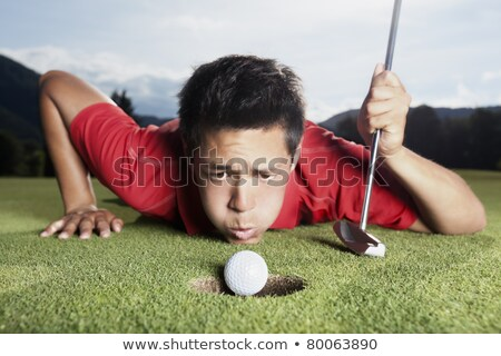 Golfer blowing ball into cup. Stock photo © lichtmeister