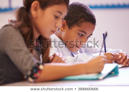 Vista lateral aluna estudar secretária sala de aula escola primária Foto stock © wavebreak_media
