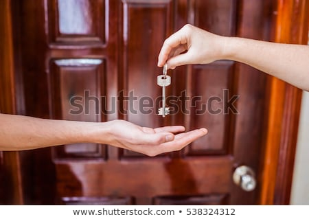 female hand holding key to the house on background of wooden door. Owning real estate concept Stock photo © galitskaya