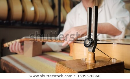 Woman Working As Lute Maker Tuning Guitar With Diapason Stock photo © diego_cervo