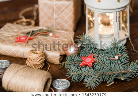 Conifer with star decoration, wrapped giftboxes, threads, candles and lantern Stock photo © pressmaster