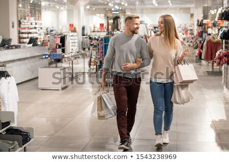 Young shoppers with paperbags leaving casualwear department in the mall Stock photo © pressmaster