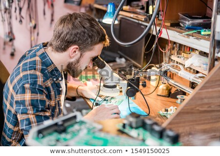 Professional gadget repairman looking in microscope while trying to find problem Stock photo © pressmaster