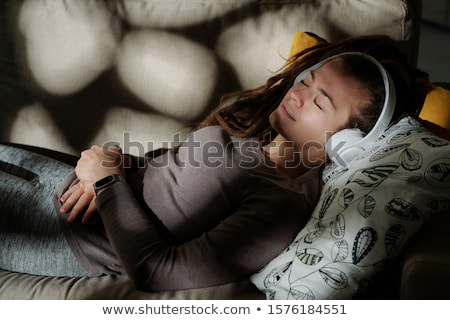 Young serene woman with headphones lying on pillow and sleeping by relax music Stock photo © pressmaster