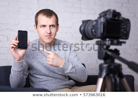 Young casual video blogger shooting new photo equipment in studio Stock photo © pressmaster