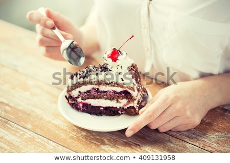 woman eating piece of layer cake with cherry Stock photo © dolgachov