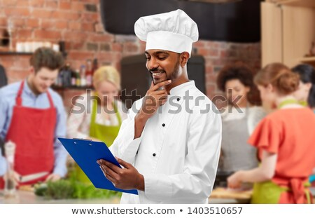 chef with menu on clipboard at cooking class Stock photo © dolgachov