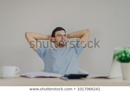 Carefree male enterpreneur ready with financial report, being glad to realize that he recieves high  Stock photo © vkstudio