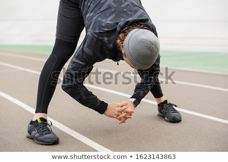 Motivated young fit sportsman working at the stadium Stock photo © deandrobot