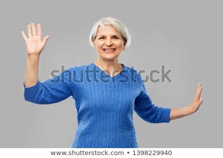 smiling senior woman touching something imaginary Stock photo © dolgachov