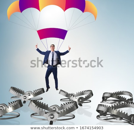 Businessman falling into trap on parachute Stock photo © Elnur