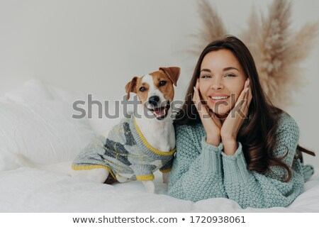Horizontal shot of lovely brunette female in casual wear, lies on white bedclothes with pedigree dog Stock photo © vkstudio