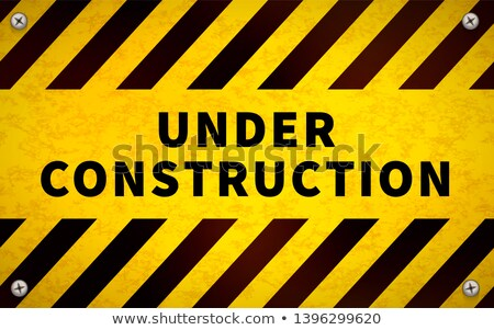 Yellow Under Construction Warning Sign With Metal Screws In Corners Stock fotó © Sarunyu_foto