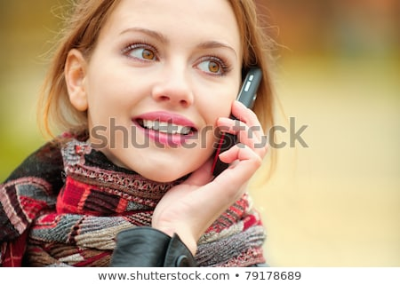 Red-haired girl calling by the phone in the autumn park. Stock photo © Massonforstock
