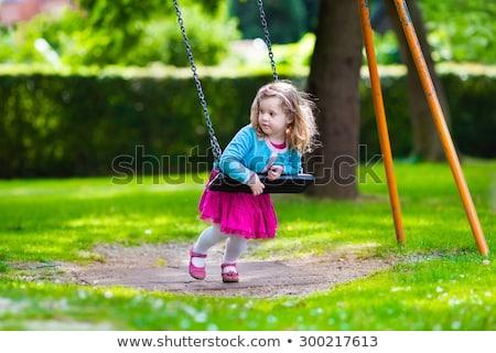 little girl playing on carousel stock photo © dacasdo