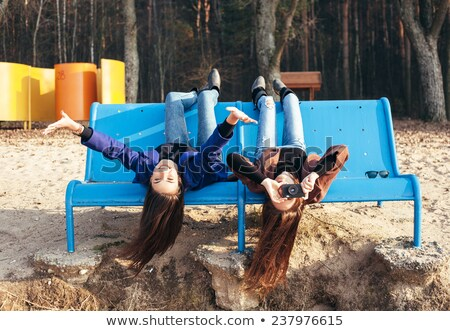 two girl friends lying down at the beach stock photo © konradbak