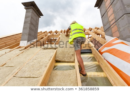 builder fitting insulation into roof of new home stock photo © highwaystarz