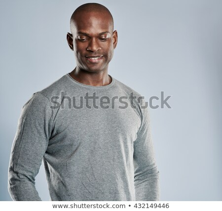 Muscular man looking downwards over gray background Stock photo © deandrobot