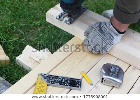 mans hand in a glove holds a working jig saw stock photo © oleksandro