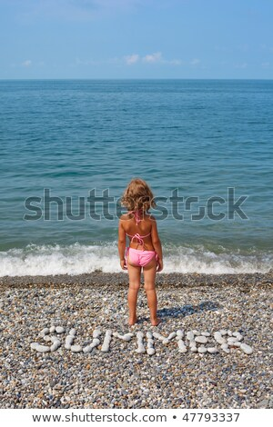 Little girl stands on beach near water. From stones word is combined 'summer'. Vertical format. stock photo © Paha_L