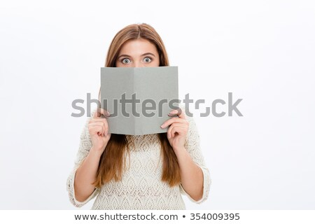 Shy embarrassed young female hiding behind grey book Stock photo © deandrobot