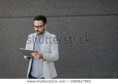 Handsome serious man with beard standing and using tablet Stock photo © deandrobot