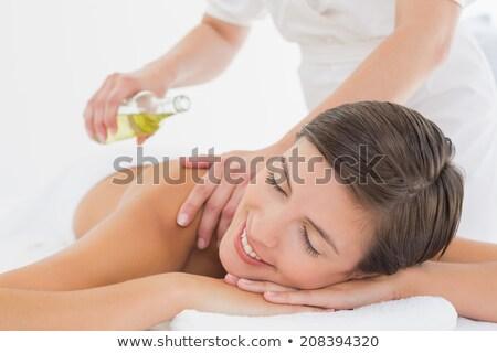 attractive woman getting massage oil on her back stock photo © wavebreak_media