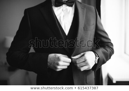elegant young business man buttoning his suit stock photo © feedough