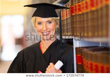 Woman in graduation cap holding book. Stock photo © RAStudio
