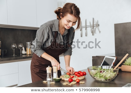 pretty woman standing in kitchen holding tomatoes stock photo © deandrobot
