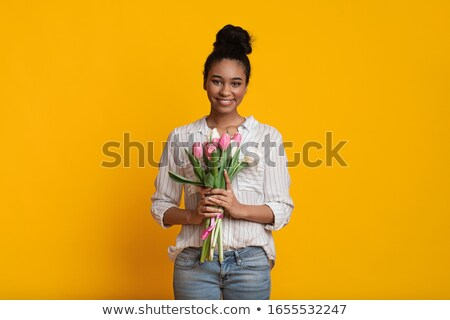 portrait of smiling woman holding gift in hands and looking to camera on black, international womens Stock photo © LightFieldStudios
