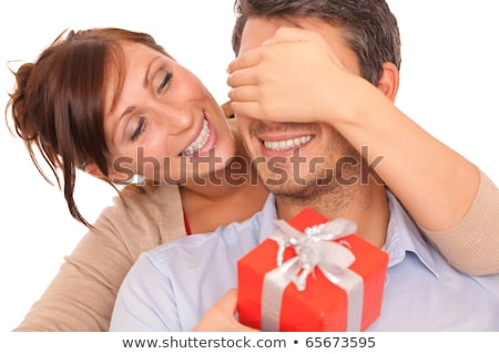 Stock photo: husband and wife holding gift kissing and smiling