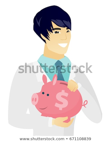 Asian doctor holding a piggy bank. Stock photo © RAStudio